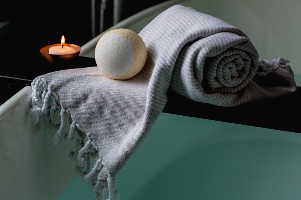 a towel and bath bomb sit on the edge of a tub to help welcome travelers home