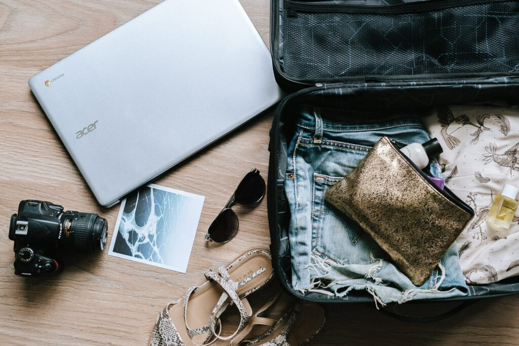 a packed suitcase lays open with a camera, sandals, sunglasses and a laptop outside of it