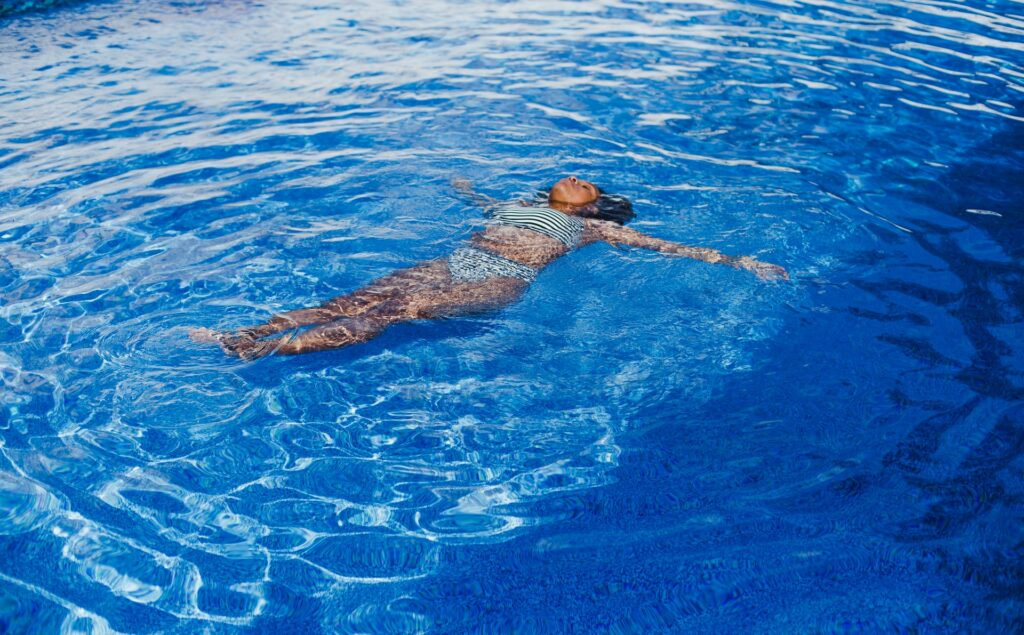 a woman lays face up in a swimming pool on a sunny day with her eyes closed
